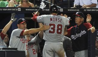 Washington Nationals' Michael Morse (38) is congratulated in the dugout after a go-ahead home run against the Atlanta Braves during the eighth inning of a baseball game, Friday, June 29, 2012, in Atlanta. Washington won 5-4. (AP Photo/John Amis)