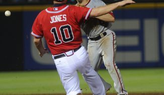 Washington Nationals second baseman Danny Espinosa sends the ball past Atlanta Braves' Chipper Jones on a double play hit into by Matt Diaz during the eighth inning of a baseball game, Friday, June 29, 2012, in Atlanta. Washington won 5-4. (AP Photo/John Amis)