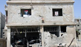 ** FILE ** Syrian security forces officers hold portraits of Syrian President Bashar Assad from the windows of their building, which was destroyed after a car bomb exploded near the shrine of Sayyida Zeinab, in a suburb of Damascus, Syria, Thursday June 14, 2012. (AP Photo/Bassem Tellawi)