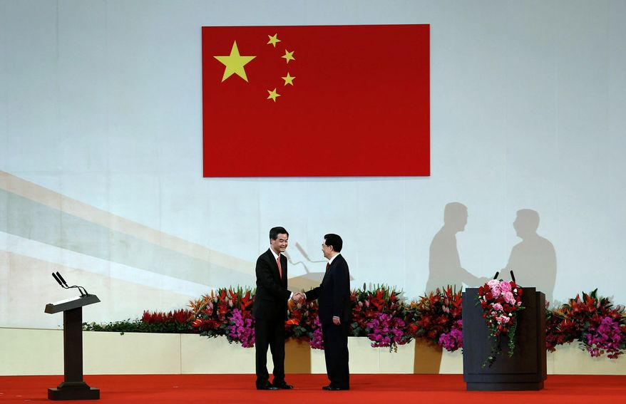 Chinese President Hu Jintao (right) shakes hands with Hong Kong's new chief executive, Leung Chun-ying, after he takes the oath of office.  (Associated Press)