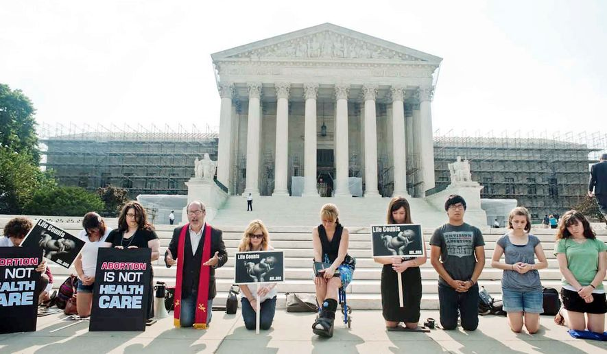 Members of Students For Life of America pray at the Supreme Court last week while waiting for a ruling on the health care reform law. The law was upheld last Thursday, and foes' attention now turns to the presidential election in November, which holds the key to the law's fate. (Raymond Thompson Jr./The Washington Times) ** FILE **
