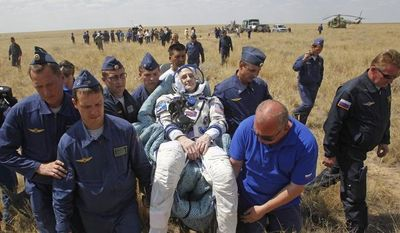 A Russian space agency rescue team carries U.S. astronaut Donald Pettit (center) shortly after the landing of the Russian Soyuz space capsule near Dzhezkazgan, Kazakhstan, on Sunday, July 1, 2012. (AP Photo/Mikhail Metzel, Pool)
