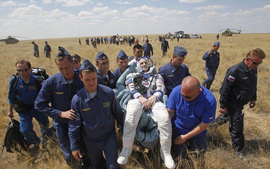 A Russian space agency rescue team carries U.S. astronaut Donald Pettit (center) shortly after the landing of the Russian Soyuz space capsule near Dzhezkazgan, Kazakhstan, on Sunday, July 1, 2012. (AP Photo/Mikhail Metzel, Pool)