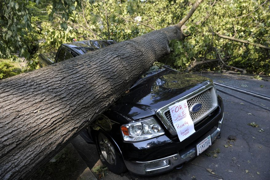 "Mike Wolfe's pickup truck lies under a fallen tree in front of his house in Falls Church, Va., on Saturday, June 30, 2012, after a severe storm Friday night. Mr. Wolfe's daughter Samanth created the ""for sale"" sign as a joke. (AP Photo/Cliff Owen)"