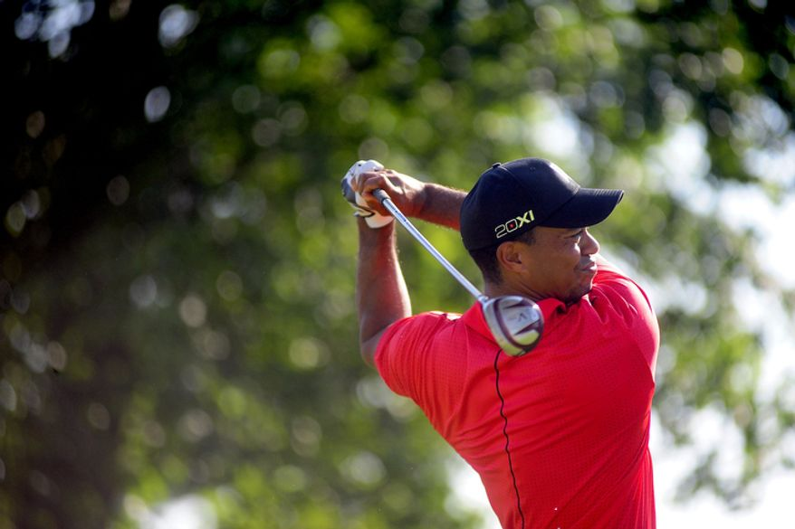 Tiger Woods hits his approach shot on the fifteenth hole at Congressional Country Club during final round play of the AT&T National golf tournament, Bethesda, Md., Sunday, July 1, 2012.  (Ryan M.L. Young/The Washington Times)