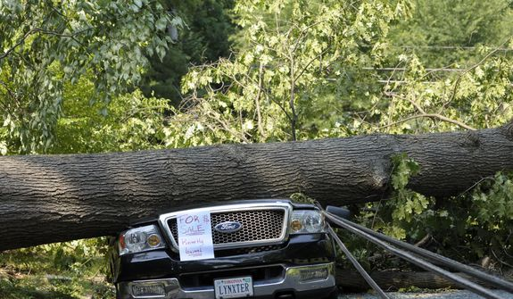 "Mike Wolfe's pickup truck lies under a fallen tree in front of his house after a severe storm in Falls Church, Va., Saturday, June 30, 2012. Wolfe's daughter created the ""for sale"" sign as a joke. (AP Photo/Cliff Owen)"