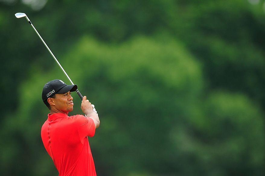 Tiger Woods hits an approach shot on the fourth hole at Congressional Country Club during final round play of the AT&T National golf tournament, Bethesda, Md., Sunday, July 1, 2012.  (Ryan M.L. Young/The Washington Times)