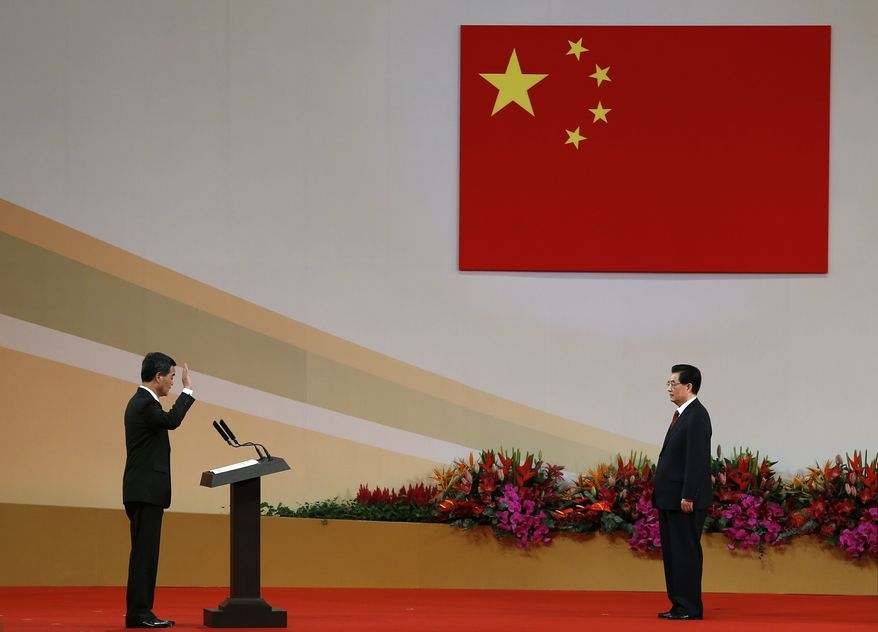 Chinese President Hu Jintao (right) administers the oath of office to Leung Chun-ying, Hong Kong's new chief executive, as he is sworn in for a five-year term at the Hong Kong Convention and Exhibition Center on Sunday, July 1, 2012. (AP Photo/Vincent Yu)