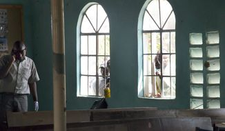 Men look in through the windows as a member (left) of the Kenyan security forces inspects the scene inside the African Inland Church in Garissa, Kenya, on Sunday, July 1, 2012, after gunmen killed at least 10 people and wounded at least 40, security officials said. (AP Photo/Chris Mann)