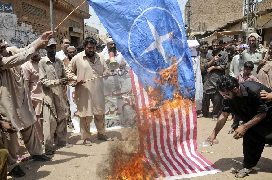 ** FILE ** Pakistani protesters burn representations of U.S. and NATO flags during a demonstration on Monday, June 4, 2012, in Multan, Pakistan, to condemn U.S. drone strikes in the tribal areas. (AP Photo/Khalid Tanveer)