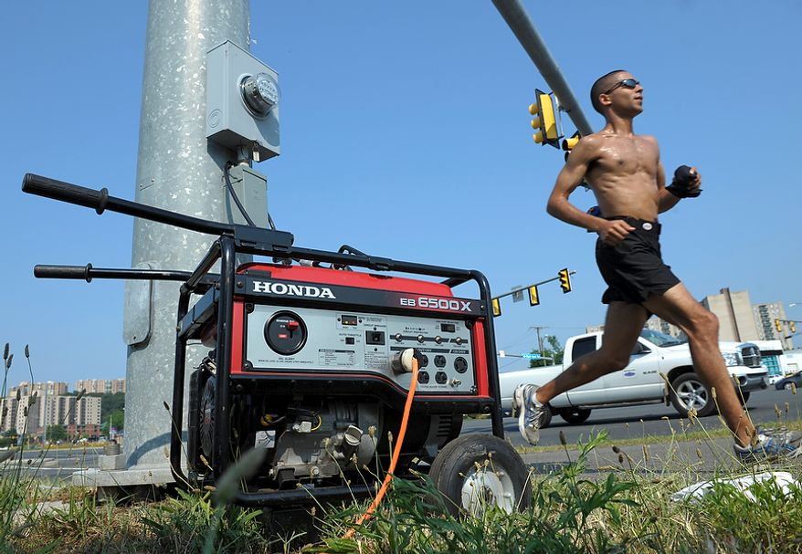 A portable generator supplies power to a traffic signal on Route 1 in Fairfax, Va., Sunday, July 1, 2012. A severe storm late Friday knocked out power to approximately a million residents, traffic signals and businesses in the Washington, DC region. (AP Photo/Cliff Owen)