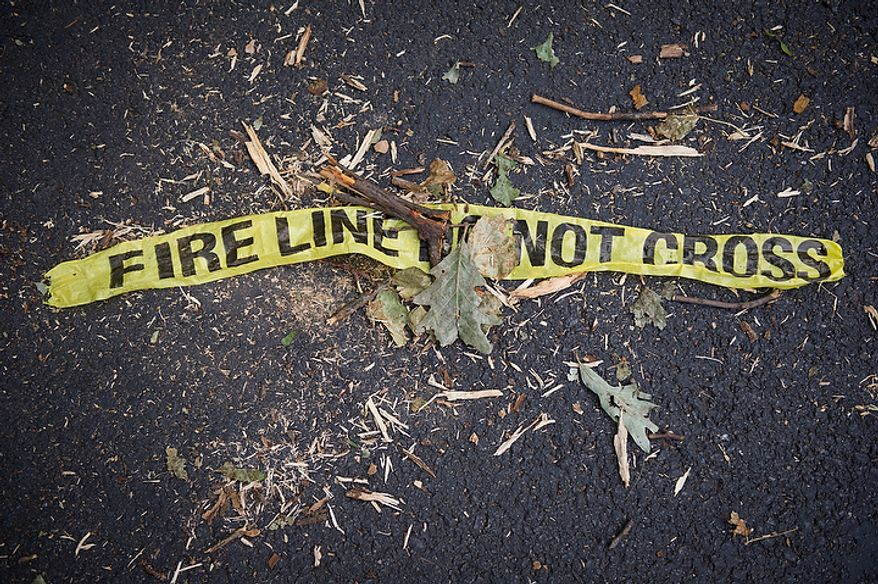 A piece of police tape lays on the ground with branches and leaves on W. Great Falls Street in Falls Church, Va., Sunday, July 1, 2012, two days after a deadly, severe storm left hundreds of thousands of people without power. (Rod Lamkey Jr./The Washington Times)