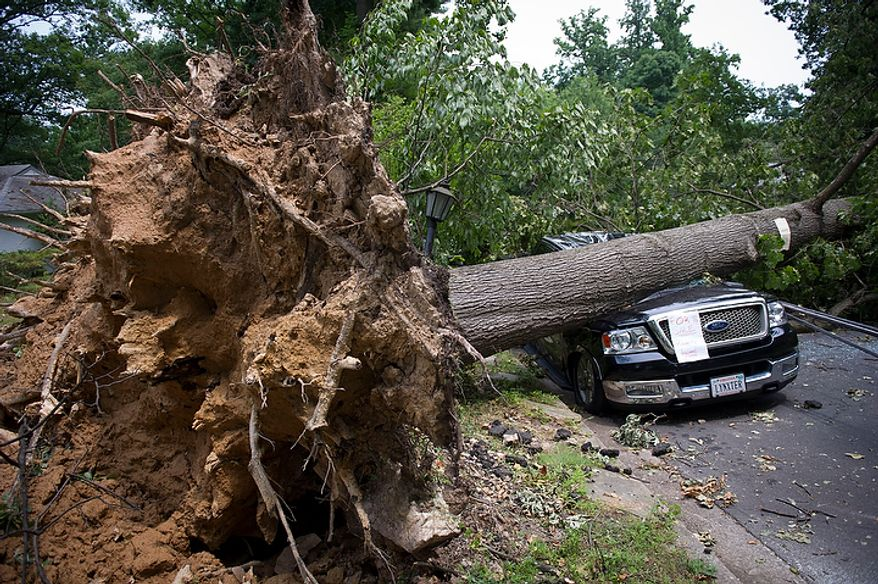 On the 300 block of N.Virginia Avenue, a Ford pick up truck belonging to Mike Wolfe remains crushed under a large fallen tree in Falls Church, Va., Sunday, July 1, 2012, two days after a deadly, severe storm left hundreds of thousands of people without power. (Rod Lamkey Jr./The Washington Times)