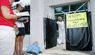 As abortion foes pray outside, Jackson Women's Health Organization owner Diane Derzis stands at the gate of Mississippi's only abortion clinic, in Jackson, Miss., on Monday. A federal judge issued a temporary restraining order Sunday that blocked enforcement of a law that could effectively regulate it out of business. (Associated Press)