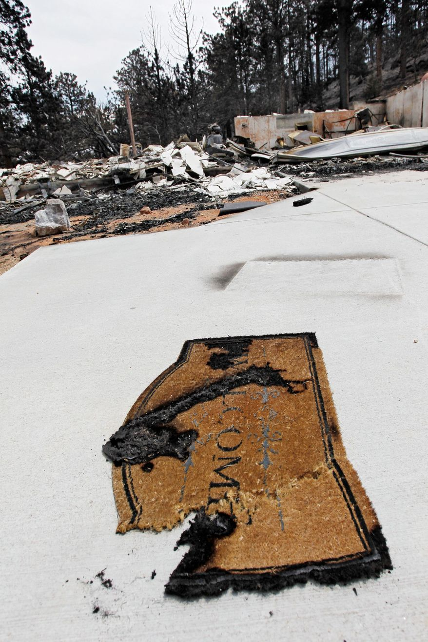 A burned welcome mat sits in front of a burned home destroyed by the High Park Fire in the Glacier View residential area near Livermore, Colo., on Monday, July 2, 2012. The last evacuees from the fire in have been allowed to return home as crews fully contained the136-square-mile wildfire that killed one resident and destroyed 259 houses. (AP Photo/Ed Andrieski)
