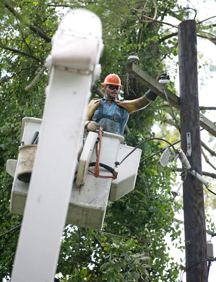 An electrical engineer from Pepco electric company attempts to repair and replace downed power lines, in Bethesda, Md., Monday, July 2, 2012. The storm left hundreds of thousands of people without power and caused wide spread property damage. (Andrew S. Geraci/The Washington Times)