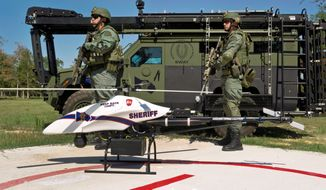 Montgomery County, Texas, SWAT team members are seen with a ShadowHawk drone from Vanguard Defense Industries. With drones becoming available for commercial use in 2015, the industry has devised voluntary standards to protect safety and privacy. (Associated Press)