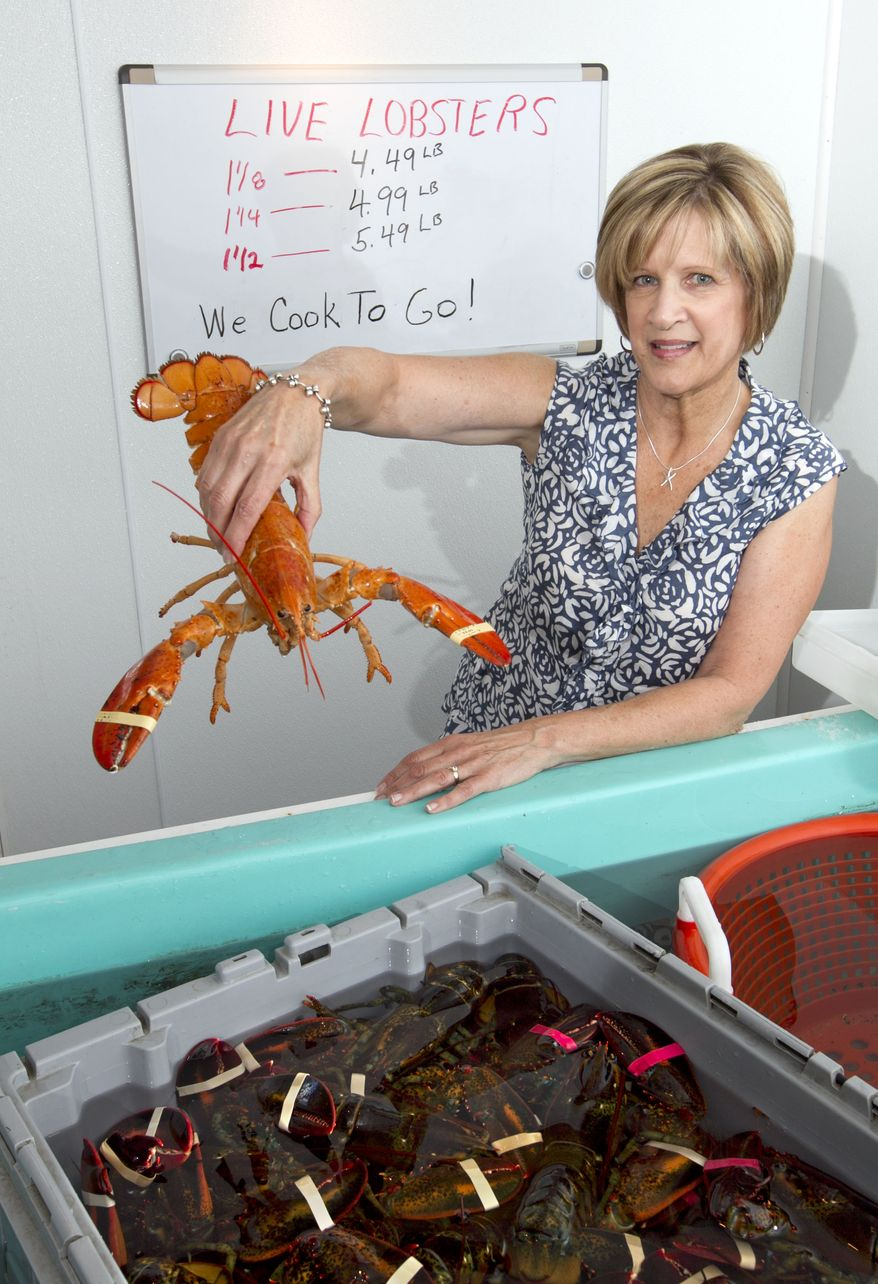 Paula Coppersmith holds a lobster at Dock's Seafood restaurant and market in South Portland, Maine, where owner Bob Coppersmith was selling five lobsters for $24 on Thursday, June 28, 2012.  (AP Photo/Robert F. Bukaty)