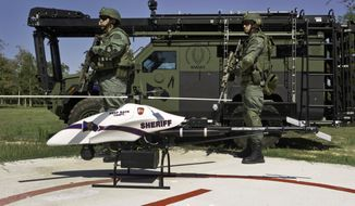 **FILE** A ShadowHawk drone is seen in September 2011 with Montgomery County, Texas, SWAT team members. (Associated Press/Vanguard Defense Industries)
