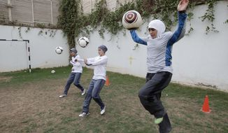 **FILE** Members of a Saudi female soccer team, including captain Rawh Abdullah (left), Rana Al Khateeb (center) and American Mawada Chaballout, practice at a secret location in Riyadh, Saudi Arabia. (Associated Press)