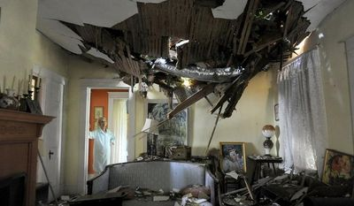 Frances Lukens looks at the tangle of boards and tree limbs piercing her living room ceiling in Lynchburg, Va., on June 30, 2012, after a huge oak tree fell directly on the house during a storm the previous night. (Associated Press/The News & Advance)