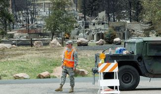 A member of the Colorado National Guard stands watch at a roadblock leading to homes in the Mountain Shadow area of Colorado Springs on Tuesday. The homes in the background are among 346 destroyed by the Waldo Canyon wildfire. (Associated Press)