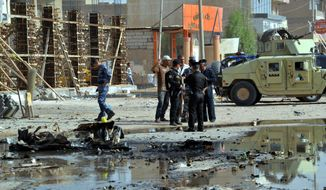 ** FILE ** Security forces inspect the scene where two car bombs exploded minutes apart in Hillah, about 60 miles (95 kilometers) south of Baghdad, Iraq, Wednesday, June 13, 2012. (AP Photo)