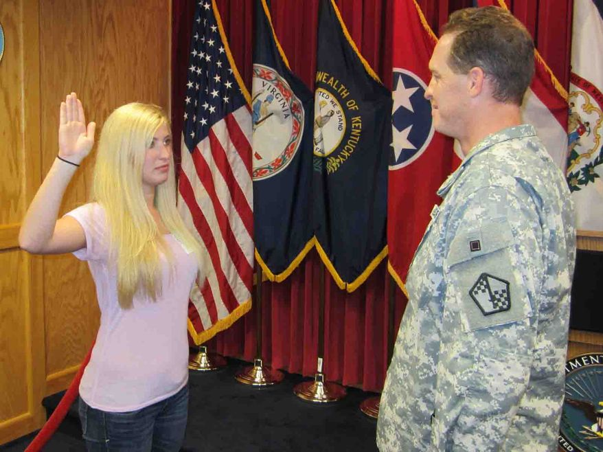Cicely Verstein is sworn into the Army at the Beckley Military Entrance Processing Station, Beckley, W. Va., by the station commander, Maj. Adam Clark, on Friday June 29. Verstein is the first woman to enlist in a combat arms support MOS since enlistment rules were changed in May.