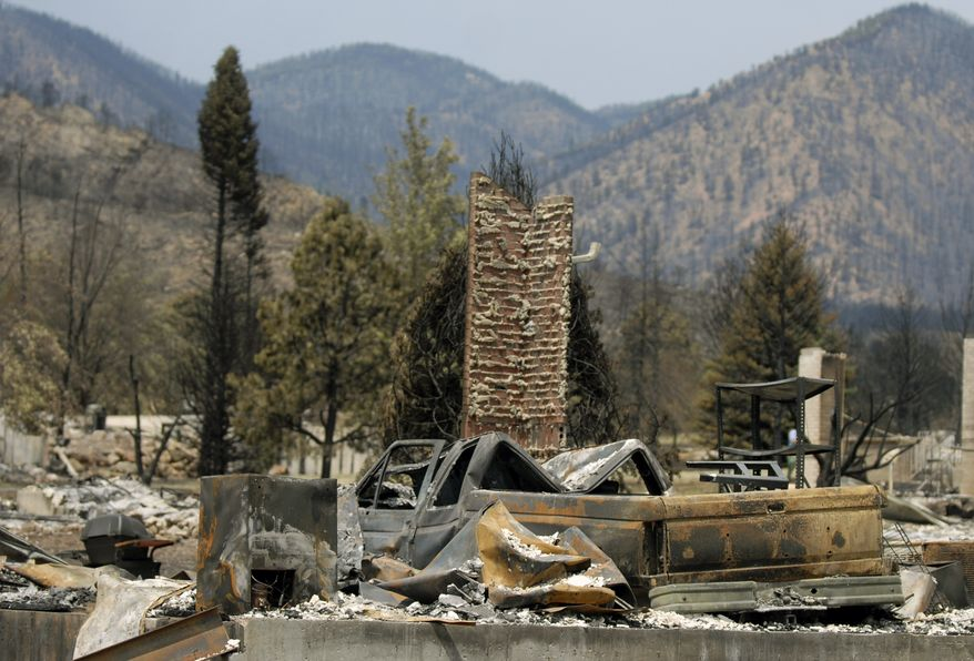 Homes are left in ruins after being destroyed by the Waldo Canyon Fire in the Mountain Shadows neighborhood of Colorado Springs, Colo., on Monday, July 2, 2012. The 28-square-mile wildfire, which has killed two people and destroyed nearly 350 homes, was 70 percent contained on Monday. (AP Photo/Bryan Oller)