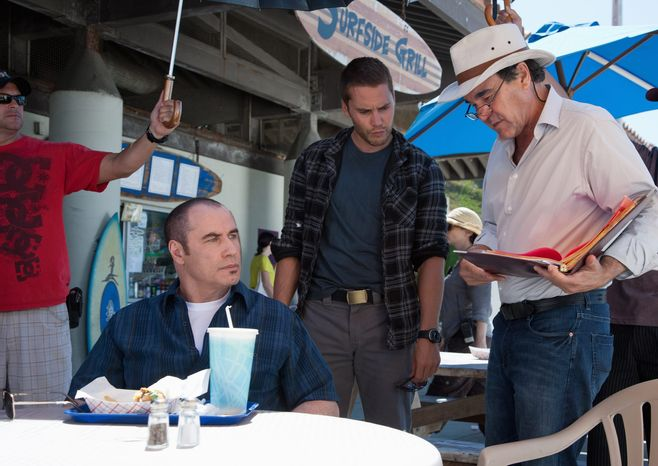 """Oliver Stone (right) works with John Travolta and Taylor Kitsch during the filming of """"Savages."""" Mr. Stone cast Mr. Kitsch after seeing his work on TV's """"Friday Night Lights"""" and an early cut of """"Battleship."""" (Universal Pictures via Associated Press)"""