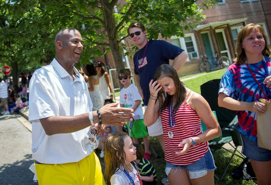 D.C. Council member Michael A. Brown (right), at-large independent, and D.C. Mayor Vincent C. Gray (far right), a Democrat, take part in the nonpartisan parade, in the Northwest neighborhood of Palisades.