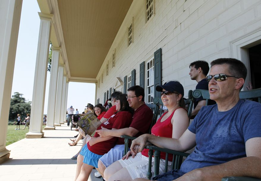 Chris Moore (right) and his wife, Dina (second from right), of Austin, Texas, enjoy the view from the veranda of the mansion at George Washington's Mount Vernon estate in Alexandria, Va., on July 4, 2012 (Associated Press)