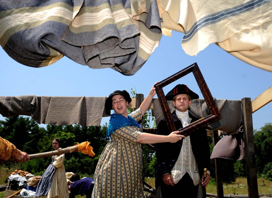 Taylor Shelby, center, portrays Dolly Madison saving the portrait of George Washington, played by Paul Luks, as another actor sets fire to the White House prop in a rehearsal for a play outlining the history of the United States, specifically the war of 1812,  on Wednesday, July 4, 2012, in Staunton, Va. (AP Photo/The Daily News Leader, Pat Jarrett)