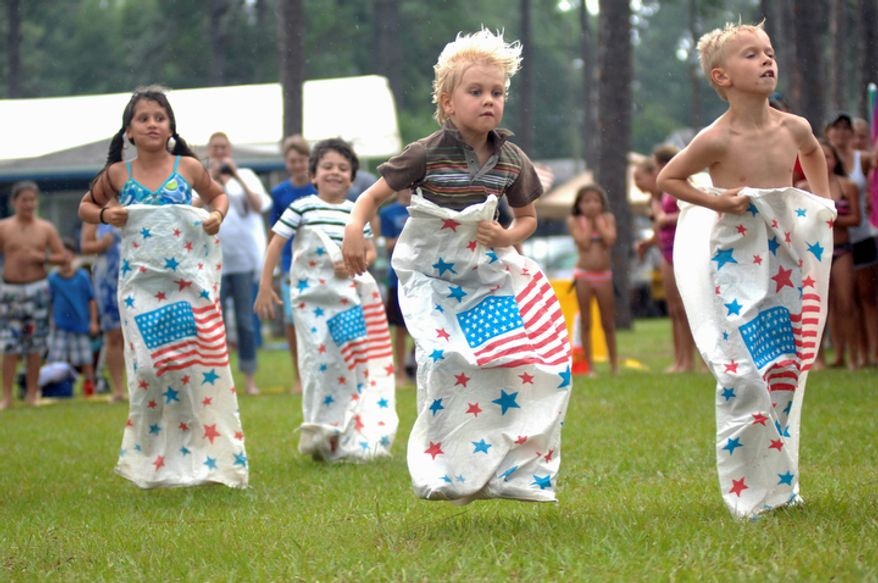 Children compete in a sack race at Lincoln Park in Valparaiso, Fla. during a Independence Day celebration. (AP Photo/Northwest Florida Daily News, Nick Tomecek)