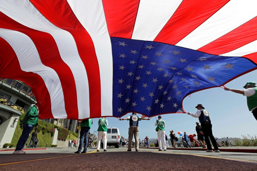 Members of the Native Sons of the Golden West carry a large American flag during the annual Fourth of July parade in Sausalito, Calif. (AP Photo/Eric Risberg)