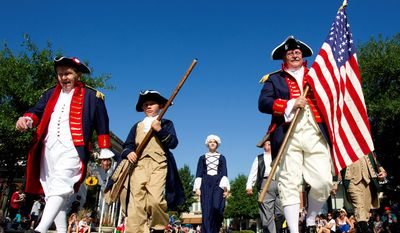 Gordon Severance, from left, Nate Eschbach, Julia Eschbach and John Kenton Thompson, of the Freedom chapter of the Sons of the American Revolution, march with the colors during the annual Fourth of July Parade at Market Street in The Woodlands, Texas. (AP Photo/Houston Chronicle, Brett Coomer)