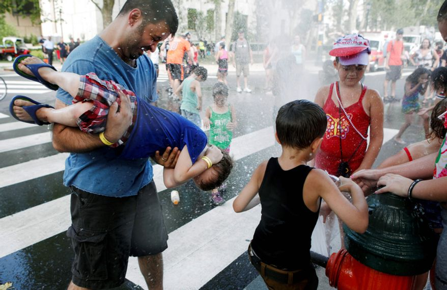 People play in the street next to a fire hydrant to keep cool during Fourth of July festivities in Philadelphia, Pa.  (AP Photo/Brynn Anderson)