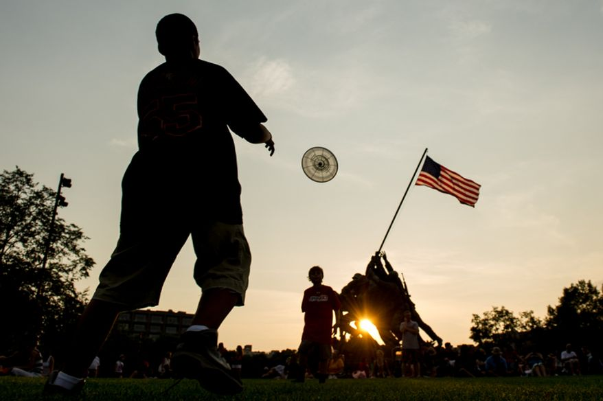 Jaden Poellot, 11, of Mt. Kisco, N.Y., left, throws a frisbee with Max Lauth, 10, second from left, of Indianapolis, Ind., in front of the Iwo Jima Memorial a few hours before fireworks are set to explode over the National Mall to celebrate Independence Day, Arlington, Va. (Andrew Harnik/The Washington Times)