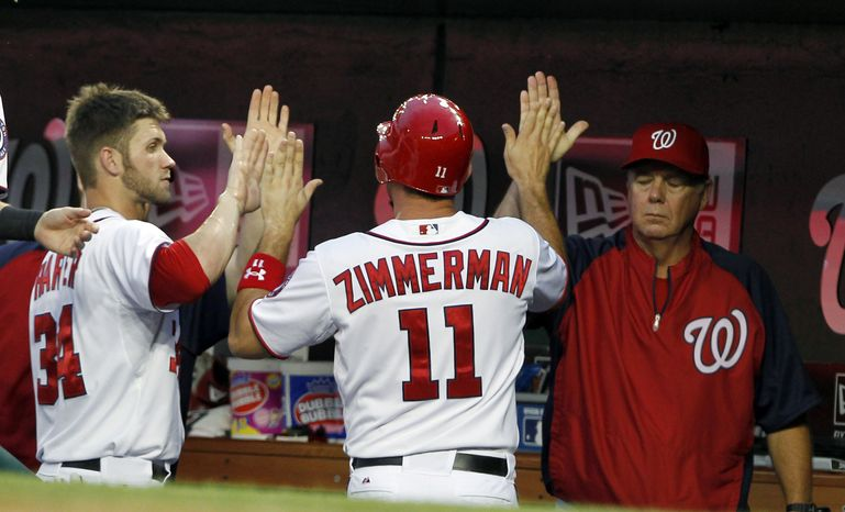Washington Nationals' Ryan Zimmerman (11) celebrates with Bryce Harper (34) and pitching coach Steve McCatty, right, after scoring during the fourth inning of a baseball game with the San Francisco Giants, Tuesday, July 3, 2012, in Washington. (AP Photo/Alex Brandon)