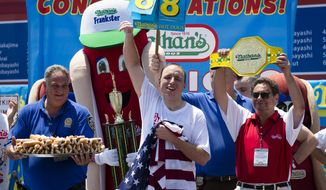 Joey Chestnut celebrates after he wins his sixth straight Coney Island hot dog eating contest on July 4, 2012, at Coney Island, in the Brooklyn borough of New York. (Associated Press)