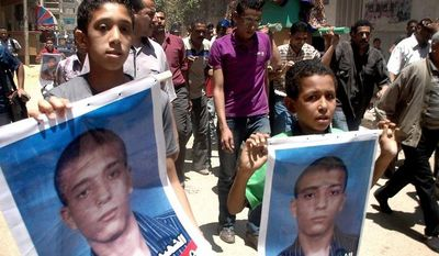 Egyptian boys hold posters of Ahmed Hussein Eid, a university student who was fatally stabbed by three suspected militants, during his funeral procession in Suez, Egypt, on July 4, 2012. (Associated Press)