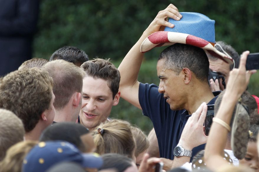 President Obama puts on a red, white, and blue hat, while visiting with service members during the Independence Day celebration on the from the South Lawn of the White House, Wednesday, July 4, 2012. (AP Photo/Haraz N. Ghanbari)