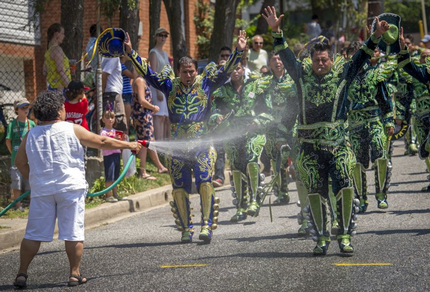 Men from the group Alma Boliviana get relief from the heat as Zanobia Patino, of Cochabamba, Bolivia, hoses them down with a garden hose as they take part in the 46th Annual Palisades Parade and Picnic in Washington, D.C., Wednesday, July 4, 2012. (Rod Lamkey Jr./The Washington Times)