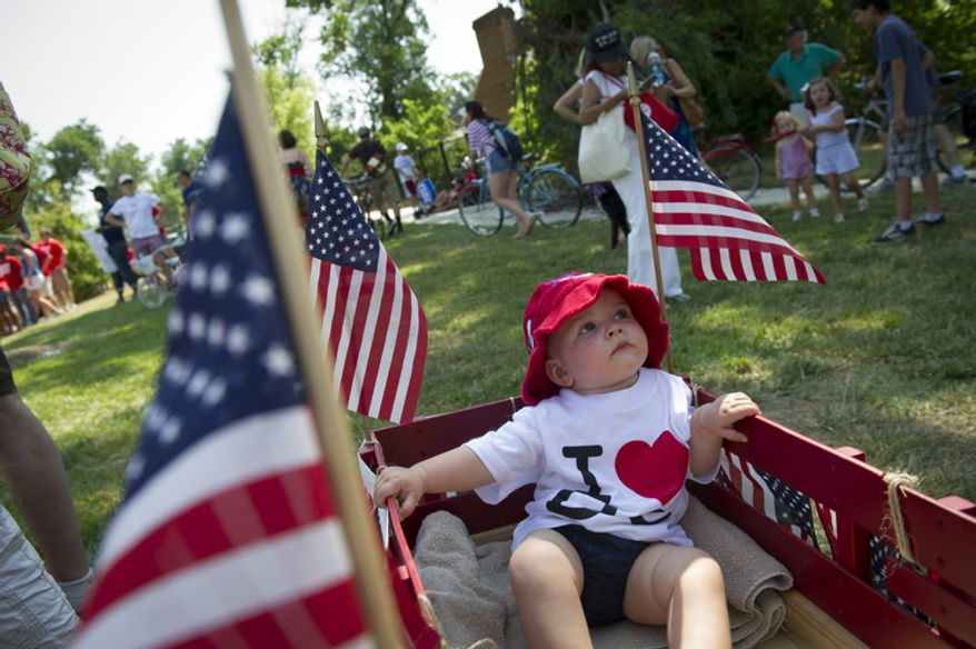 Asher Stroh, 1, of Washington, D.C., waits in the wagon to be led into the 46th Annual Palisades Parade and Picnic. (Rod Lamkey Jr./The Washington Times)