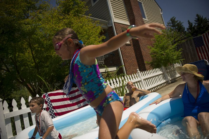 The Ettinger family (left to right) Jack, 7,  Sarah, 8, husband Jason and mom Susan, watch the passing of the 46th Annual Palisades Parade and Picnic in Washington, D.C., Wednesday, July 4, 2012, from their front yard pools. (Rod Lamkey Jr./The Washington Times)