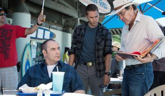 "Actors John Travolta (left) and Taylor Kitsch (center) confer with director Oliver Stone during the filming of ""Savages.""The movie, which opens Friday, also stars Salma Hayek and Benicio Del Toro. (Universal Pictures)"