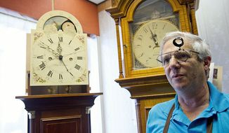 Danny Sobel, whose family owns the Clock Shop in Vienna, Va., stands by two grandfather clocks in his shop. The one on the left was was made by Pennsylvania craftsman David Lindow, who with his son and a part-time employee builds about 125 clocks in a typical year. (Barbara L. Salisbury/The Washington Times)