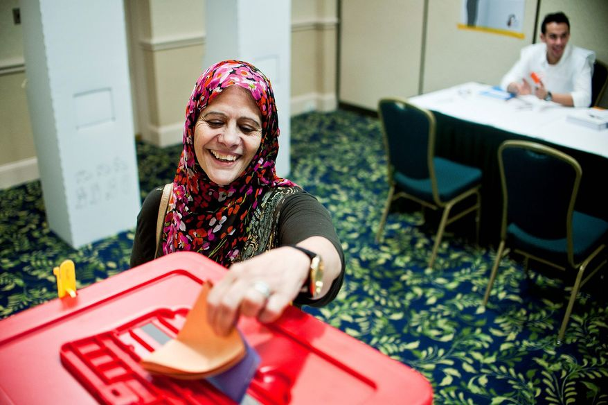 "Teffaha Abeidi, 58, of Fairfax casts her ballot at the Holiday Inn in Arlington on Tuesday, the first time the native of Libya had voted in her lifetime. ""I'm so excited, my legs are still shaking,"" she said. (Ryan M.L. Young/The Washington Times)"