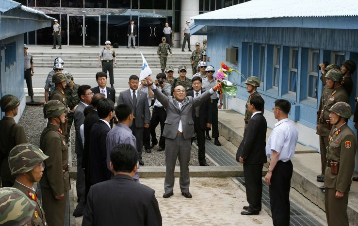 """Activist No Su-hui (center) shouts, """"Long live reunification!"""" in front of North Korean officials and soldiers before crossing the demarcation line between North and South Korea where South Korean officials (in background) were waiting for him, at the Demilitarized Zone at Panmunjom, Korea, on Thursday, July 5, 2012. South Korean officials immediately detained the activist for making an extended trip to Pyongyang without South Korean government approval, as required by law. (Associated Press)"""