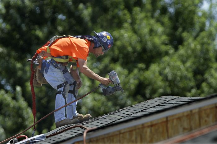 **FILE** A construction worker wearing a safety harness installs roofing tiles June 27, 2012, in Springfield, Ill. (Associated Press)